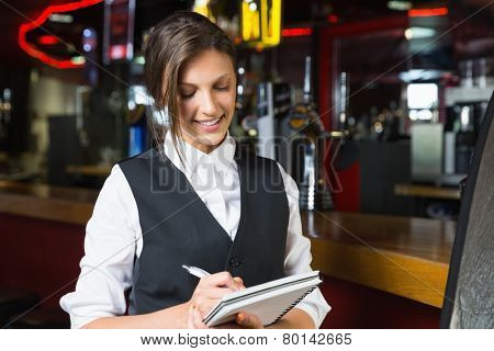 Happy barmaid writing in notepad in a bar