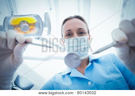Low angle portrait of female dentist in surgical mask holding dental tools