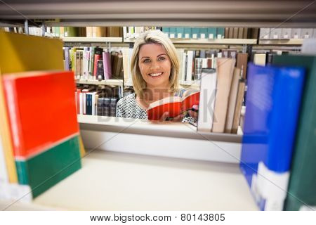 Mature student reading a book in library at the university