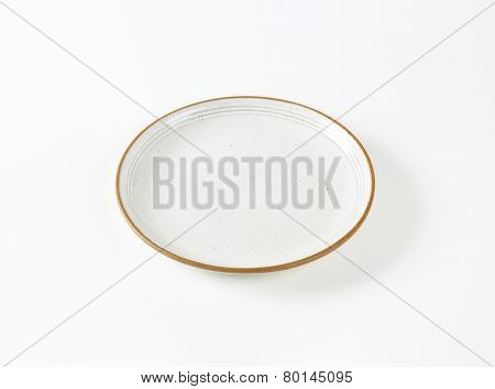 white soup plate with brown rim on white background