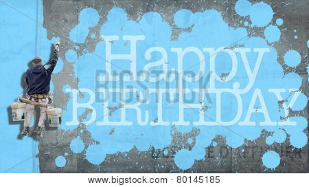 Painter hanging from harness painting a wall with the word Happy Birthday in blue