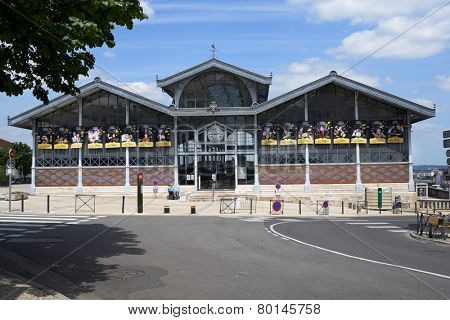 ANGOULEME, FRANCE - JUNE 26, 2013: Man in wheelchair in front of the covered market. Made of architectural glass and iron in 1886, the building is a national historic monument