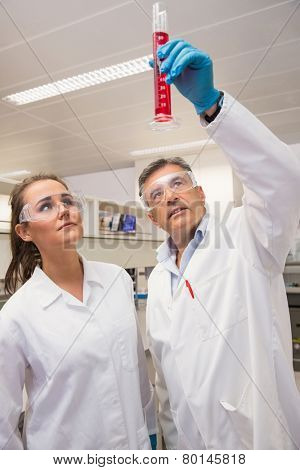 Pharmacists looking at beaker of red liquid at the laboratory