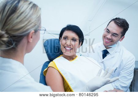 Portrait of smiling male dentist and assistant with female patient in the dentists chair