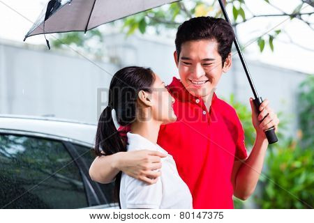 Asian man with umbrella walking woman in rain from car door to house