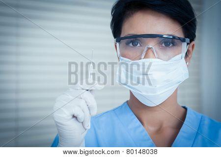 Portrait of female dentist in surgical mask holding dental tool