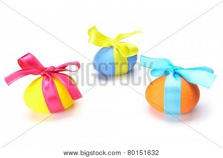 Close-up of colorful Easter eggs tied up by silk ribbons