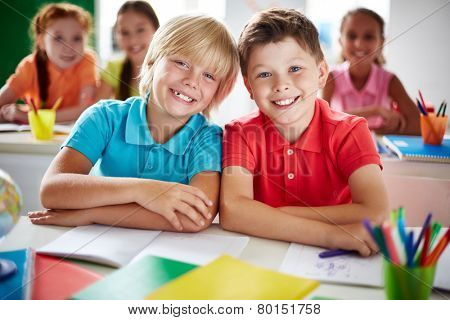 Two cheerful schoolboys looking at camera in classroom