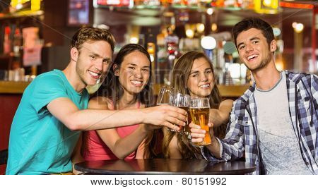 Portrait of happy friends toasting with drink and beer in a pub