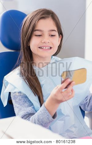 Young patient looking in the mirror in dental clinic