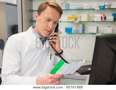 Serious pharmacist on the phone at the hospital pharmacy