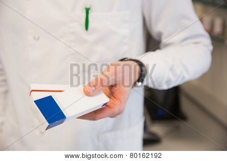 Pharmacist holding medicine boxes at the hospital pharmacy