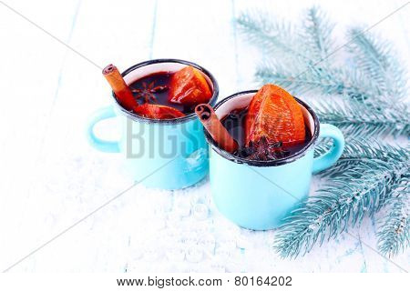 Mugs of mulled wine with pieces of orange and spice on snow covered background
