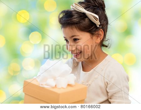 holidays, children, christmas, people and birthday concept - happy little girl with gift box over green lights background