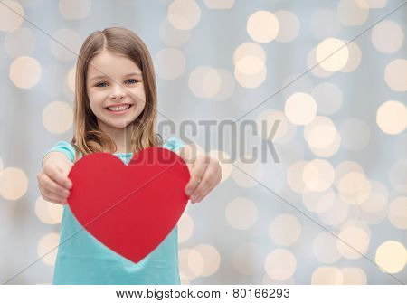 love, charity, holidays, children and people concept - smiling little girl with red heart over light