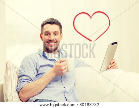 technology, home and lifestyle concept - smiling man working with tablet pc computer and coffee cup at home