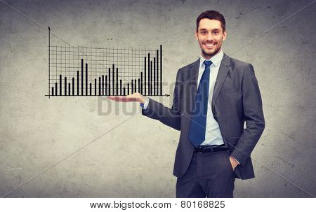 business, office, advertising and people concept - friendly young buisnessman showing growing chart on the palm of his hand