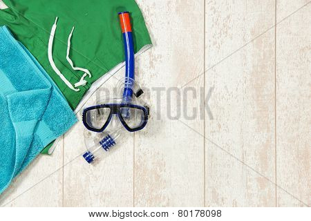 Directly above shot of swimming trunks; towel and snorkeling mask on floorboard