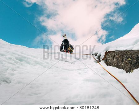 Ice climbing: mountaineer on a mixed route of snow and rock during the winter. Western Alps, Italy, Europe.