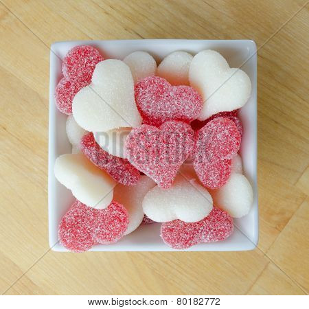 Red And White Gummy Hearts In White Bowl On Butcher Block