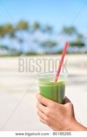 Green vegetable smoothie - healthy eating concept. Close up of green vegetable detox smoothie with spinach. Woman hand holding vegetable smoothies outside on summer beach.