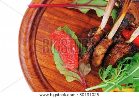 main portion : grilled ribs on woden plate isolated over white background with salad leaves and red grapefruit