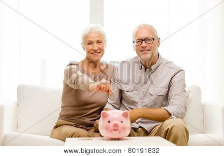 family, savings, age and people concept - smiling senior couple with money and piggy bank at home