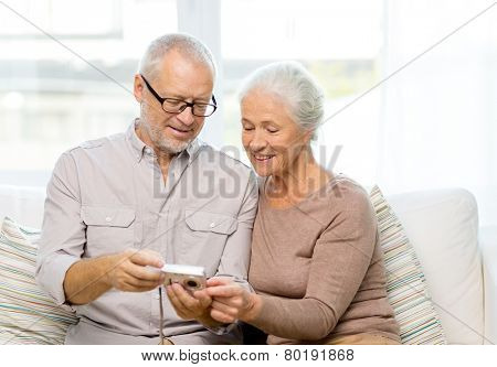 family, technology, age and people concept - happy senior couple with camera at home