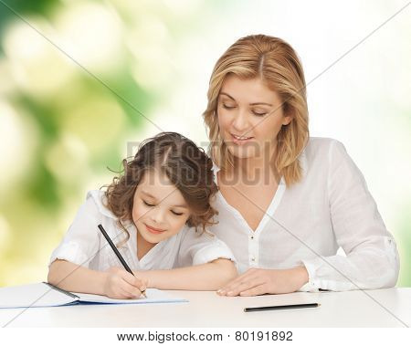 people, family, school, home education and parenting concept -happy mother and daughter doing homework and writing in notebook over green background