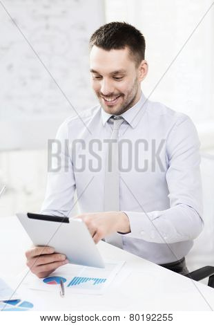 office, business, technology, finances and internet concept - smiling businessman with tablet pc computer and documents in office