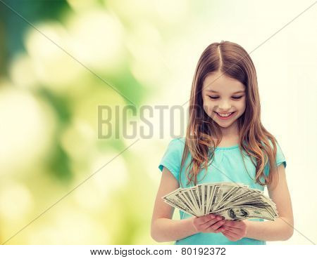 money, finances and people concept - smiling little girl looking at dollar cash money