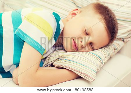health, sleeping and dreaming concept - little boy sleeping at home