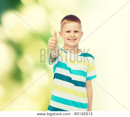 happiness, childhood, ecology and people concept - smiling little boy in casual clothes showing thumbs up over green background