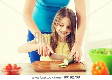 family, child, cooking and home concept - smiling little girl with mother chopping cucumber in the kitchen