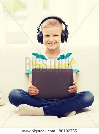 home, childhood, leisure, technology and music concept - smiling little boy with tablet pc computer and headphones at home