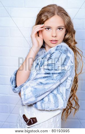 Fashion shot of a pretty teenager girl with beautiful long curly hair wearing white knitted dress and fur jacket. Beauty, fashion.