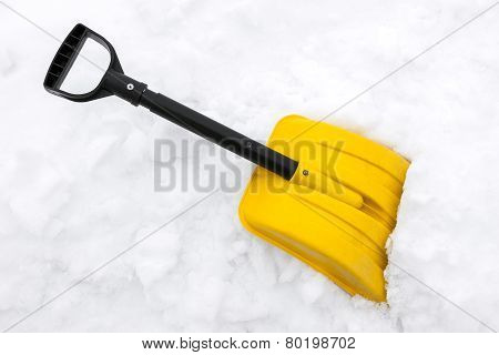 Yellow Snow Shovel On White Snow