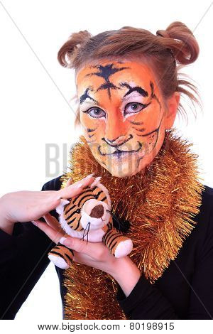 Girl in appearance a tiger with a toy tiger cub.