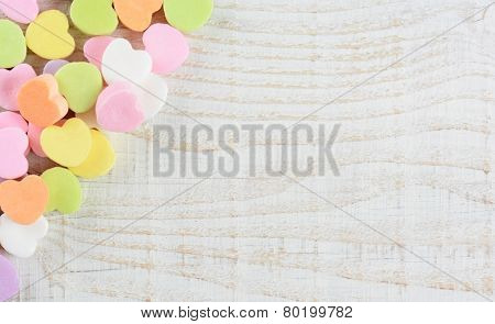 Overhead shot of a group of pastel candy Valentine's hearts in the upper right corner and side of the frame. Horizontal format on a whitewashed rustic wooden table with copy space.