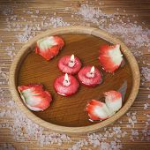 stock photo of unity candle  - Spa concept with rose petals salt and burning candles that float in a wooden bowl with water imitation filter instagram - JPG