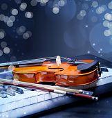 stock photo of violin  - Violin and piano keys on black - JPG