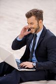 foto of motivation talk  - Cheerful young businessman working on laptop and talking on the mobile phone while sitting on sand - JPG