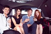 stock photo of limousine  - Happy friends drinking champagne in limousine on a night out - JPG