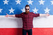 pic of open arms  - Handsome young bearded man in glasses keeping arms opening and looking at camera while standing against American flag - JPG