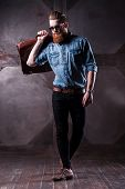 pic of shot glasses  - Handsome young bearded man in glasses making a step while holding a suitcase on his shoulder - JPG