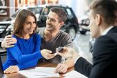 stock photo of rental agreement  - Car salesman giving the key of the new car to the young attractive owners - JPG