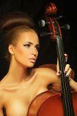 foto of cello  - Photo golden beautiful female musician playing a cello - JPG