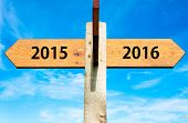 stock photo of opposites  - Wooden signpost with two opposite arrows over clear blue sky year 2015 and 2016 signs Happy New Year conceptual image - JPG