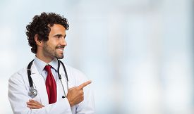 stock photo of finger  - Portrait of a smiling doctor pointing his finger - JPG