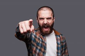 pic of shout  - Furious young bearded man pointing you and shouting while standing against grey background - JPG